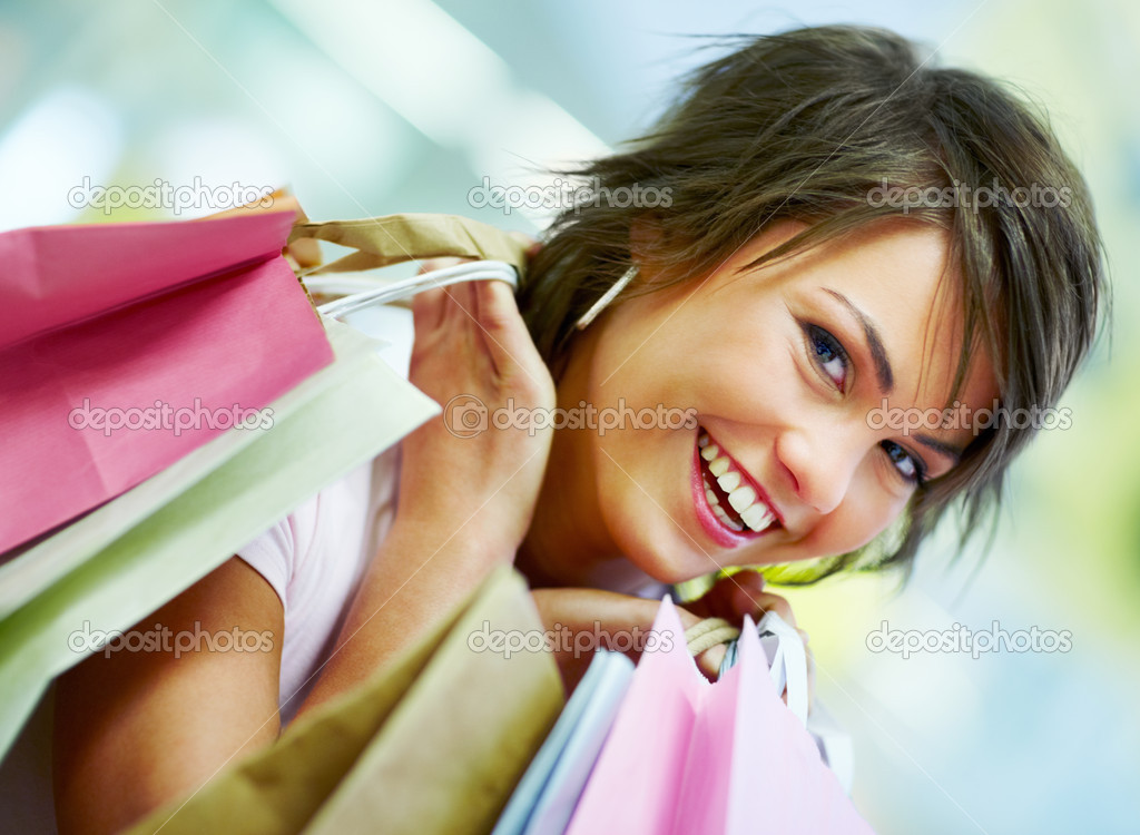 Portrait of a cute young woman holding shopping bags — Stock Photo #3300554