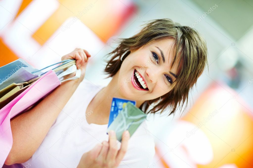 Portrait of a happy young woman holding shopping bags and credit cards  Foto Stock #3300584