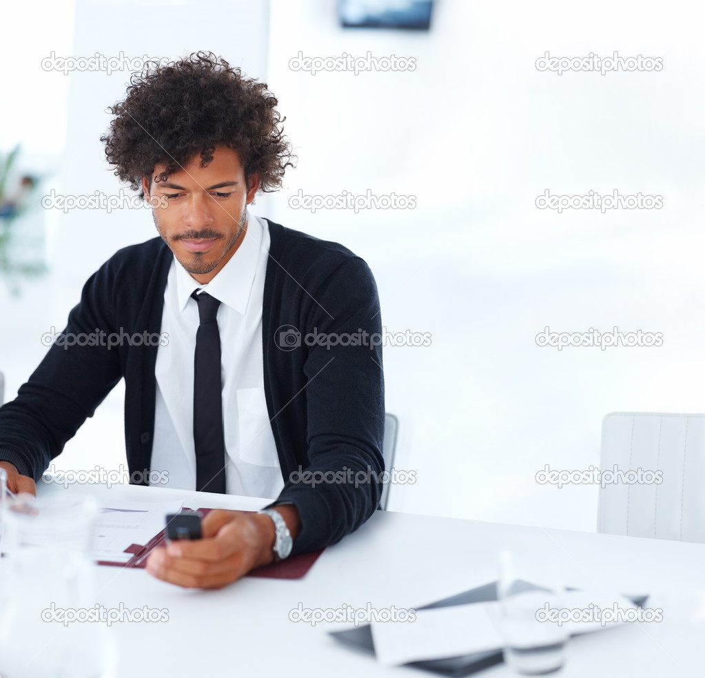 Portrait of a young business man sitting on the desk and using his cellphone — Stock Photo #3301450