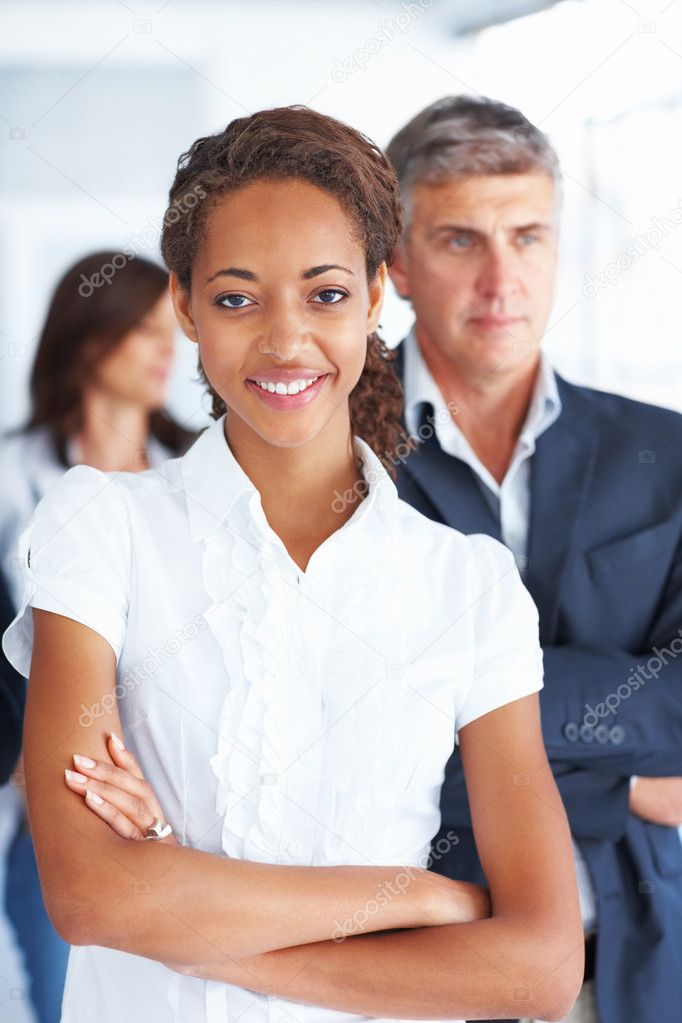 Portrait of a young business woman with her hands folded and other colleagues at the back — Stock Photo #3301512