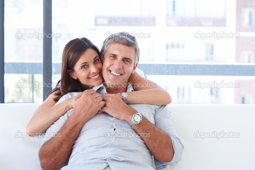 Cute cheerful gorgeous smiling couple sitting on a sofa  Stock Photo #3301631
