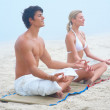 Happy young man and woman sitting at the beach in the lotus posi - Stok fotoğraf