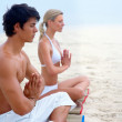Young man and woman sitting at the beach practicing yoga togethe - Stok fotoğraf
