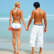 Rear view of a cute couple holding eachothers hand at the beach - Stock Photo