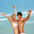 Royalty-Free Stock Photo: Happy young couple at the beach with their hands raised