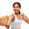 Royalty-Free Stock Photo: Young female boxer with closed fist smiling over white