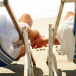 Young couple holding hands while resting on deck chairs by the b - Stock Photo