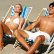 Young couple relaxing on a deck chair and getting themselves tan - Stock Photo