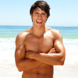 An attractive masculine man posing at the sea shore - Stockfoto