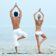 Young man and woman practicing yoga at the beach - Stock Photo