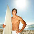 A young man standing with a surfboard - Stock Photo