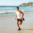 Young male athlete running on the sea shore - Stock Photo