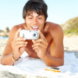 Young lying down on the beach and viewing his digital camera - Стоковая фотография