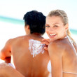 Pretty woman in a playful mood with her boyfriend at the beach - Stock Photo