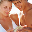 Royalty-Free Stock Photo: Cute couple holding a star fish at the beach
