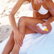 Pretty woman sitting on the beach and applying body lotion befor - Stock Photo