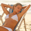 Young female in white bikini by the shore resting on a deck chai - Stock Photo