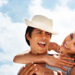 Cute young couple having fun with the blue sky as the background - Stock Photo