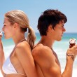 Profile image of a couple at the beach having an ice cream - Stock Photo