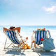 Couple on a deck chair relaxing on the beach - Stok fotoğraf