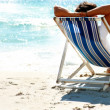 Couple on a deck chair relaxing on the beach, rear view - Stock Photo
