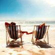 A couple resting on the deck chairs - Stock Photo
