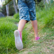 Low section of a child with a backpack climbing uphill - Foto Stock