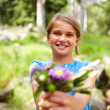 Happy small girl offering a bouquet of flowers - Stockfoto