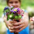 Blurred image of a small girl offering a bunch of flowers - Stockfoto