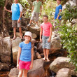 Royalty-Free Stock Photo: Group of happy young children standing by a stream, outdoors