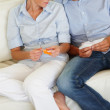 Young couple relaxing on the sofa and deciding on the color sche - Stock Photo