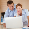 Royalty-Free Stock Photo: A beautiful couple at home working on a laptop