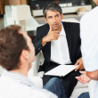 Successful consultant discussing investment plans with a couple - Stock Photo