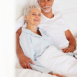 Royalty-Free Stock Photo: A happy old couple relaxing on the bed