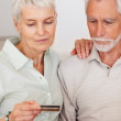 Royalty-Free Stock Photo: Happy elderly couple purchasing from the net using a credit card