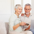 Cute elderly couple at home shopping with their credit card from - Stock Photo