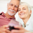 Cute old couple enjoying a glass of wine with eachother - Stock Photo