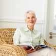 Royalty-Free Stock Photo: Cute senior lady reading a book while sitting on a cane chair