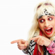 Royalty-Free Stock Photo: Crazy young rockstar pointing towards copyspace, isolated agains