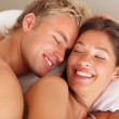 Happy man and woman enjoying in bed - Stock Photo