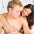 Happy young couple in a good mood on bed - Stock Photo