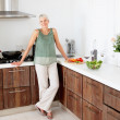 Royalty-Free Stock Photo: Happy senior woman standing isolated in the kitchen