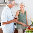 Happy senior couple preparing food in the kitchen - Stock Photo