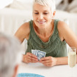 Senior woman playing a game of cards with a person - Stock Photo