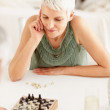 Happy senior woman chess player during a game - Stock Photo