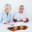 Royalty-Free Stock Photo: Happy elderly couple enjoying fruits and juice while still in be