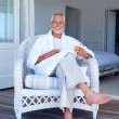 Elderly man sitting on a chair holding a croissant - Photo