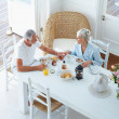 An aged couple enjoying their breakfast at home - Photo