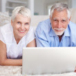 Royalty-Free Stock Photo: Mature couple lying on the floor, using a laptop