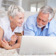 Happy elderly couple purchasing from the net using a credit card - Stock Photo